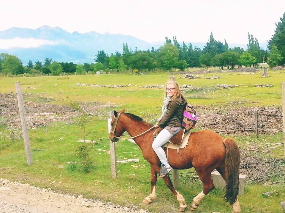Horseback rider in front of grassy field
