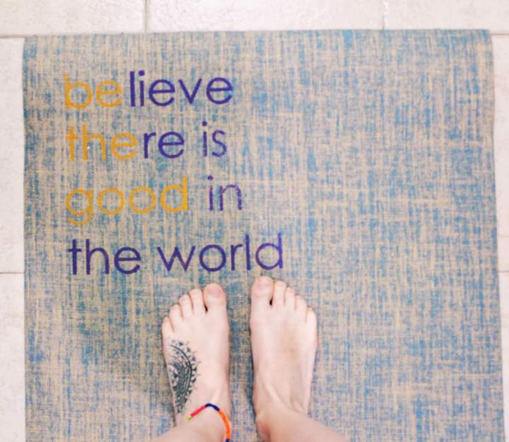 Tattooed feet on a yoga mat with a quote