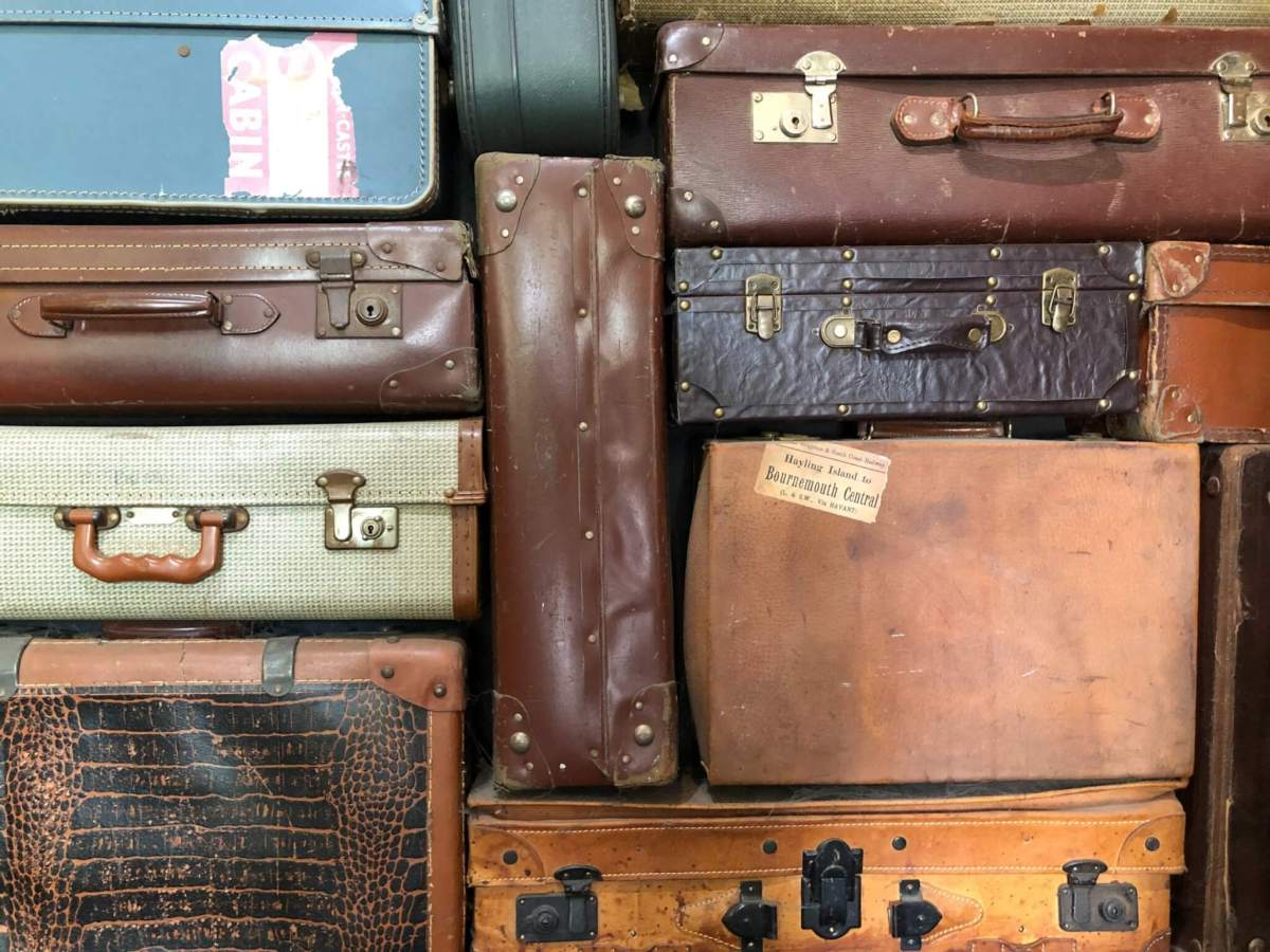 Suitcases Versus Carry On Luggage | Eco-Friendly Travel | Suitcases stacked on one another