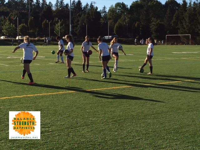 Image of girls warming up on a soccer field