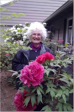 Image of Laura Coleman's client Juanita in her garden with flowering rhodedendron
