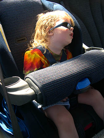 Image of a child asleep in a in car seat with mouth hanging open, probably snoring