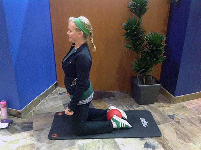 Image of Laura Coleman demonstrating kneeling ankle squeezes