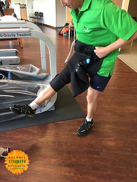 Image of man pulling on neoprene shorts for air treadmill workout