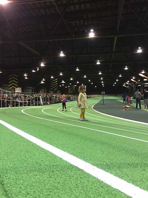 image of a small girl on an indoor running track