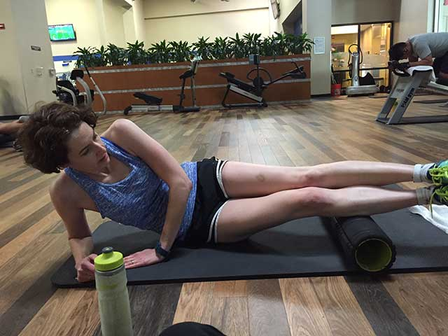 Image of a woman rolling her calf muscles on a foam roll