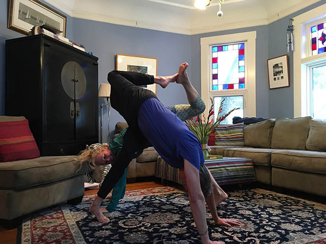 Image of personal trainer, Laura Coleman doing a partner scorpion dog stretch