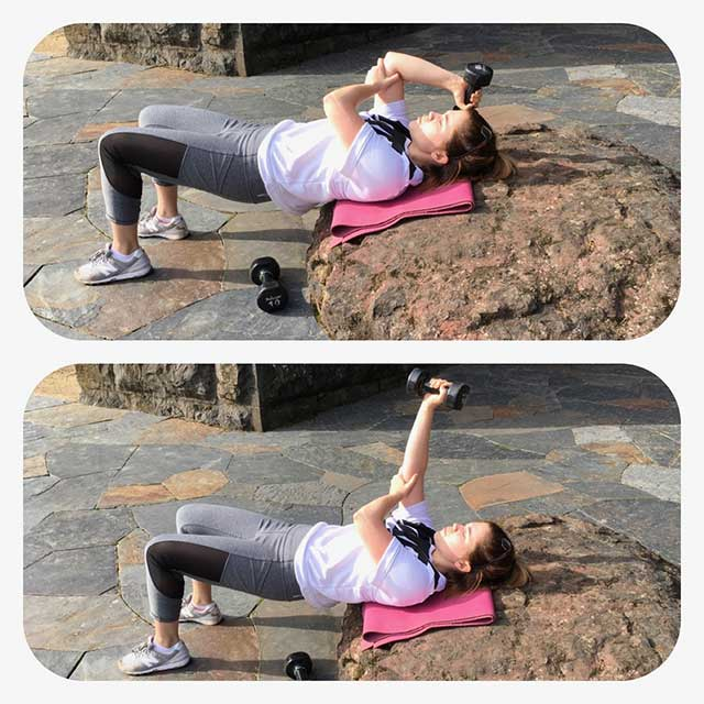 Image of woman in a shoulder bridge doing shoulder extensions with weights