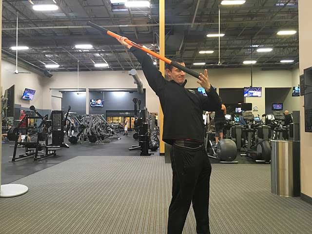 Image of man demonstrating shoulder exercise using a moving stick in a gym