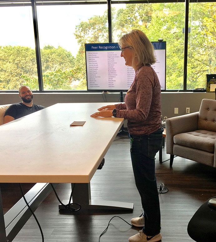 Image of a woman standing at a work desk