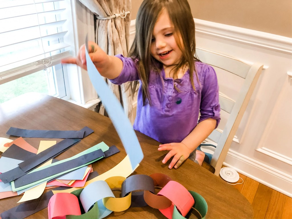 Teach your child colors, patterns, and numbers by making a quarantine paper chain with your toddler as an indoor activity when you're stuck at home.
