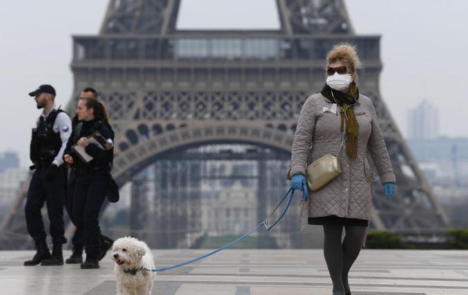 A Parisien wears protective gear near the Eiffel Tower