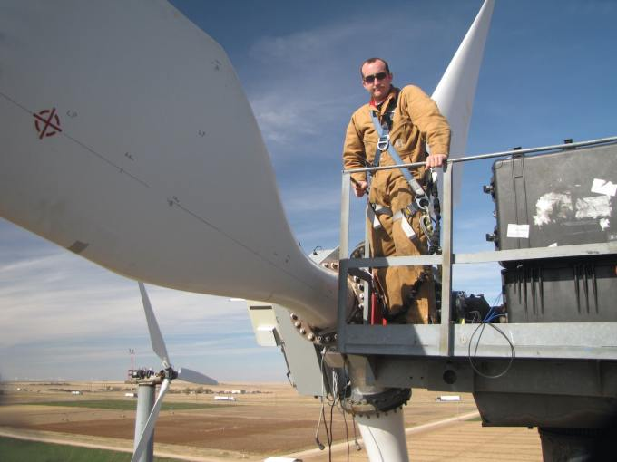 Worker stands at the top of a wind turbine during installation.
