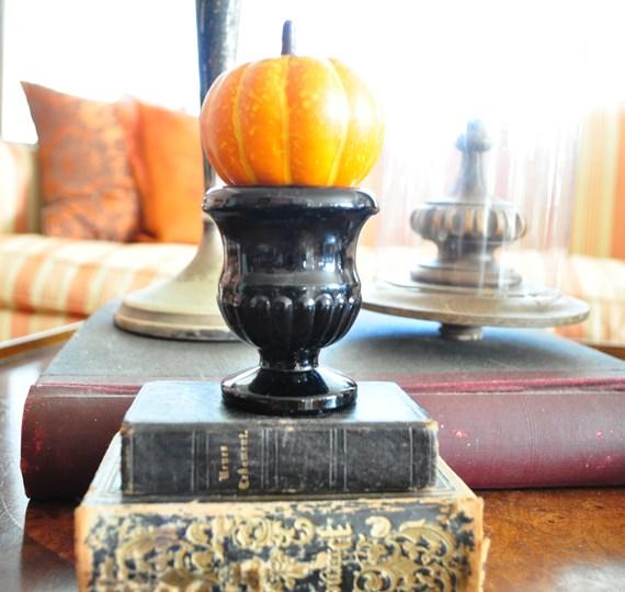 Small pumpkin on top of black glass match holder