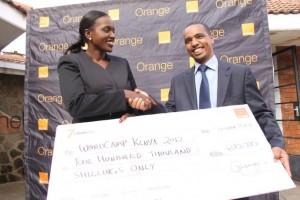 dAVID mUGO RECEIVES A CHEQUE FROM oRANGE tElkom's Angela Nganga for Wordcamp Kenya 2012