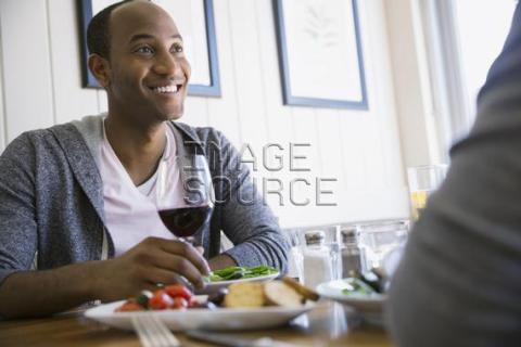 Man drinking wine at bistro table