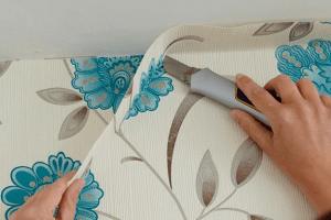 persona recortando papel tapiz con navaja