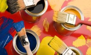 botes de pintura de varios colores con brochas