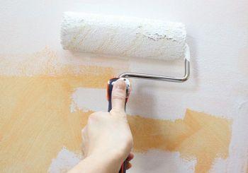persona pintando madera con rodillo