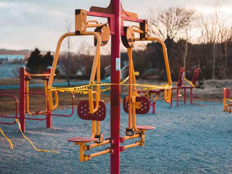 swing on sandy playground under cloudy sky
