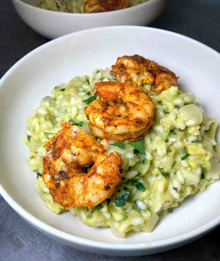 Avocado risotto in a white bowl with blackened shrimp