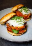 two chicken parmesan burgers on a plate