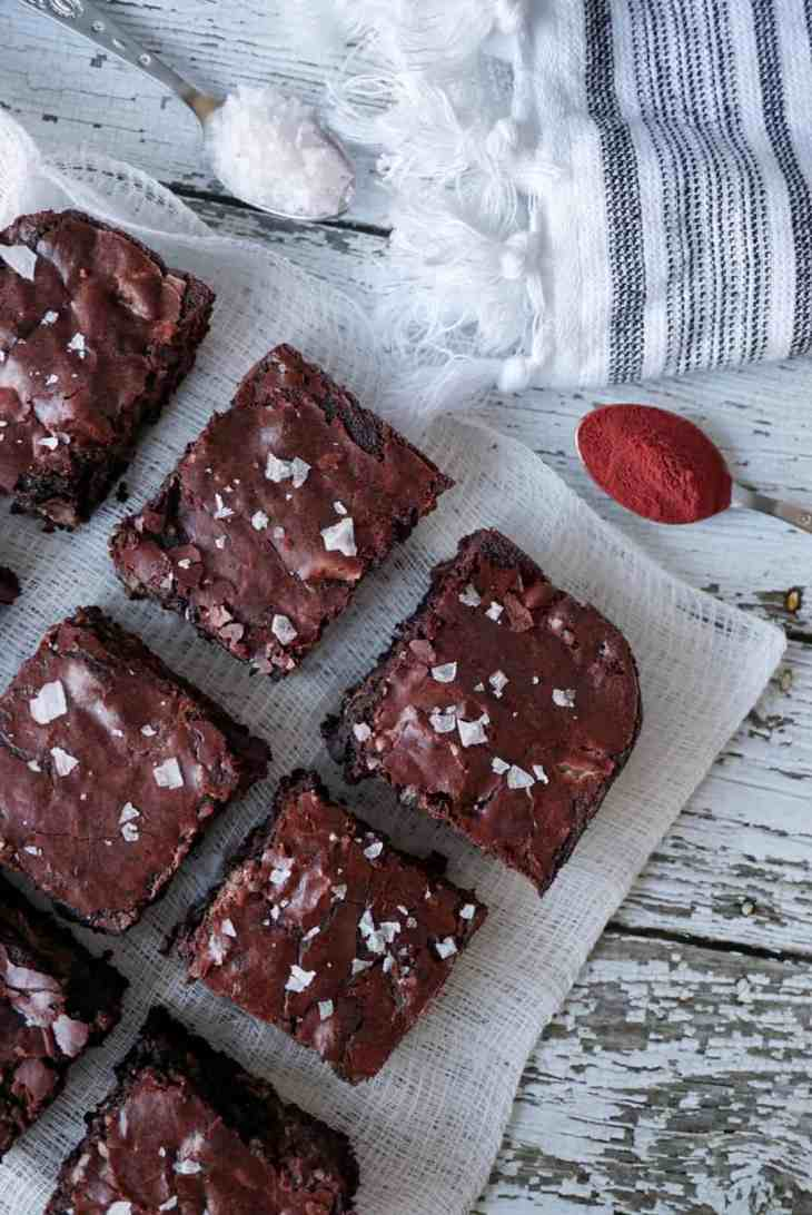 Brownies on a cheese cloth with two spoons of flaky salt and beetroot powder