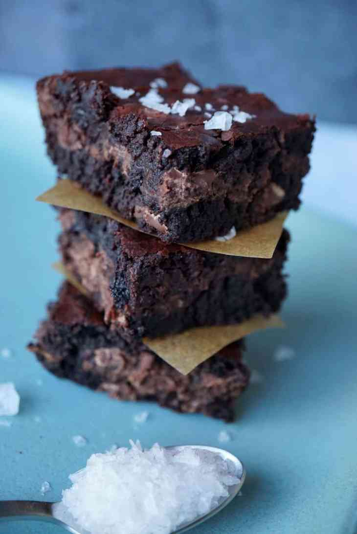 Three brownies stacked with a spoon of flaky salt