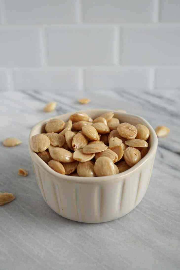 Marcona almonds in a white bowl on marble counter