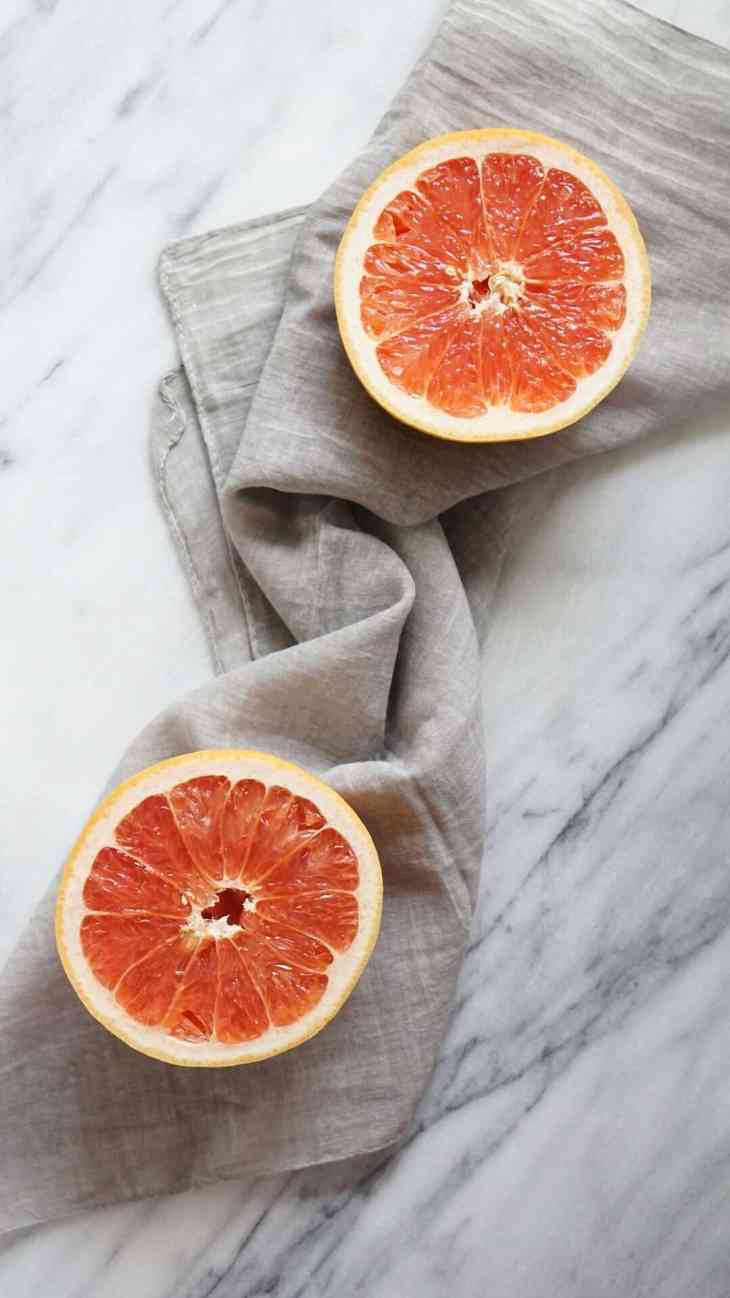 Two grapefruit halves on a grey napkin with a marble background