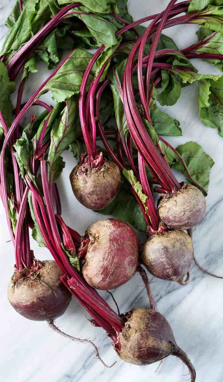 Six beets bunched together on a marble slab