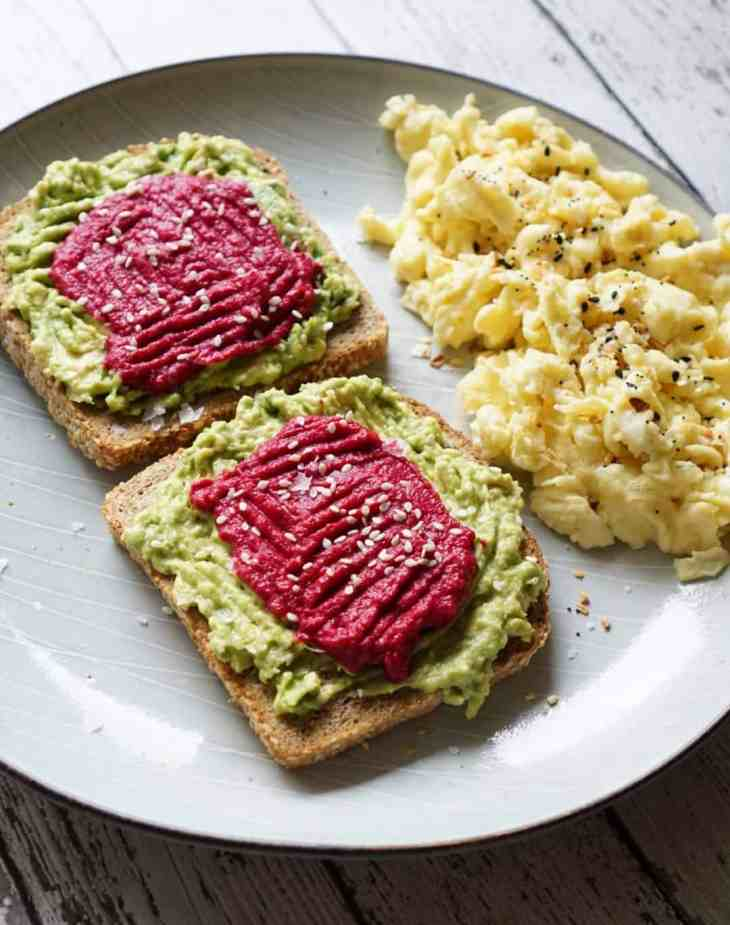 Avocado toast with scrambled eggs on a grey plate
