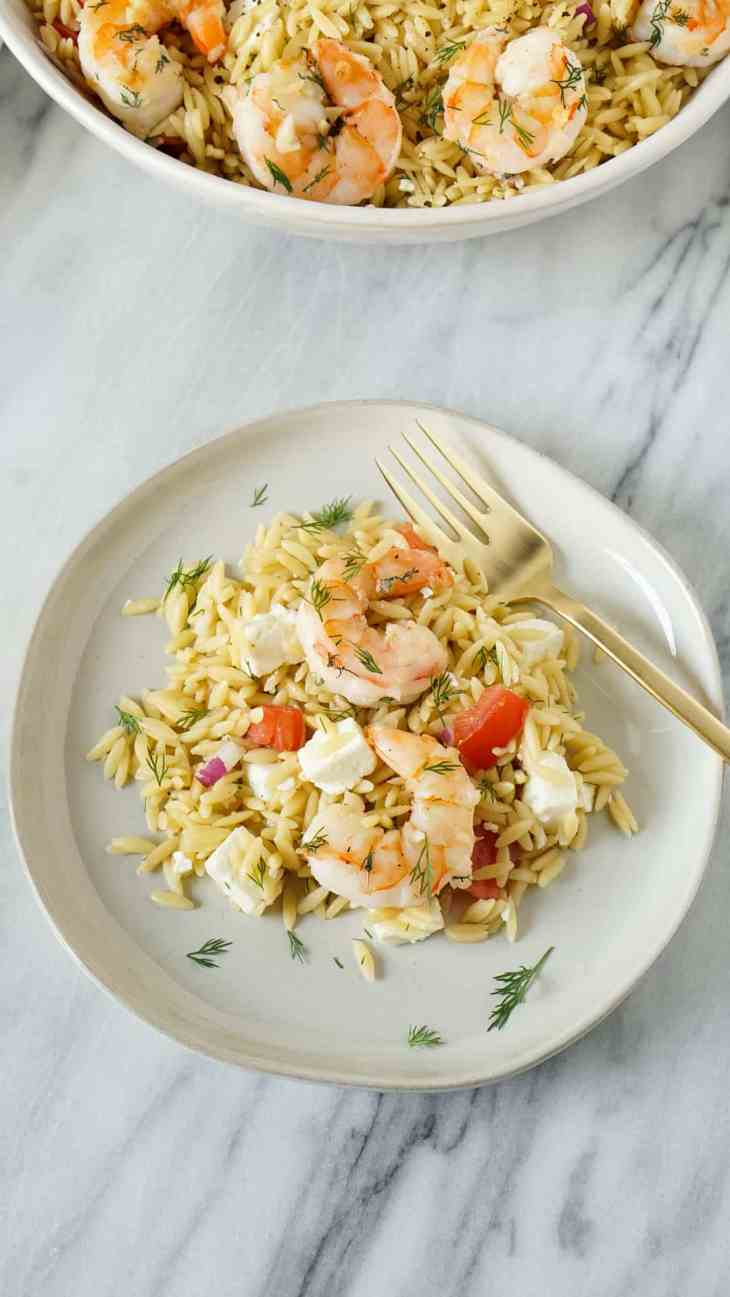lemon orzo salad with garlic butter shrimp on a white plate