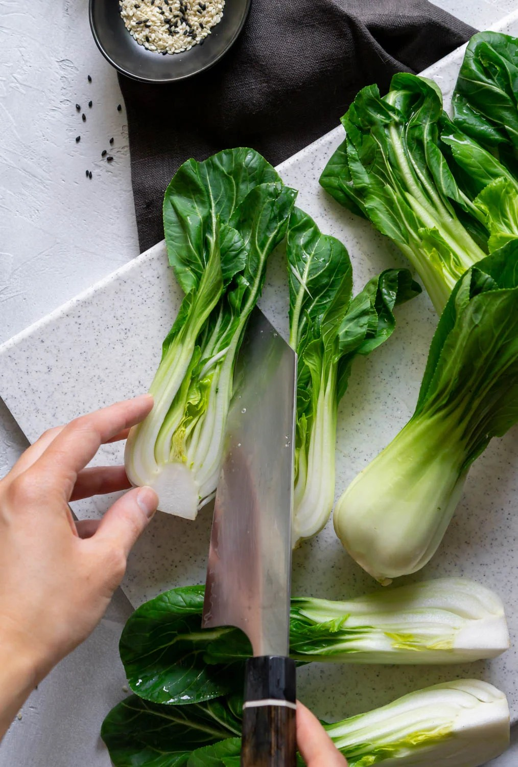 sliced bok choy, a hand, and a chef's knife