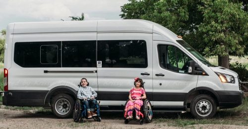 Image of a boy in a wheelchair smiling with a button up shirt and a girl in a wheelchair with a pink dress smiling in front of a large white accessible van