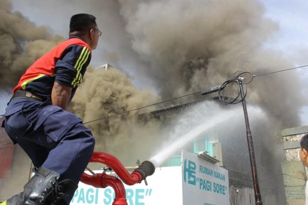 Petugas tengah memadamkan api terhadap kebakaran Rumah Makan Pagi Sore, Pondok, Kota Padang. FOTO/YATHADA