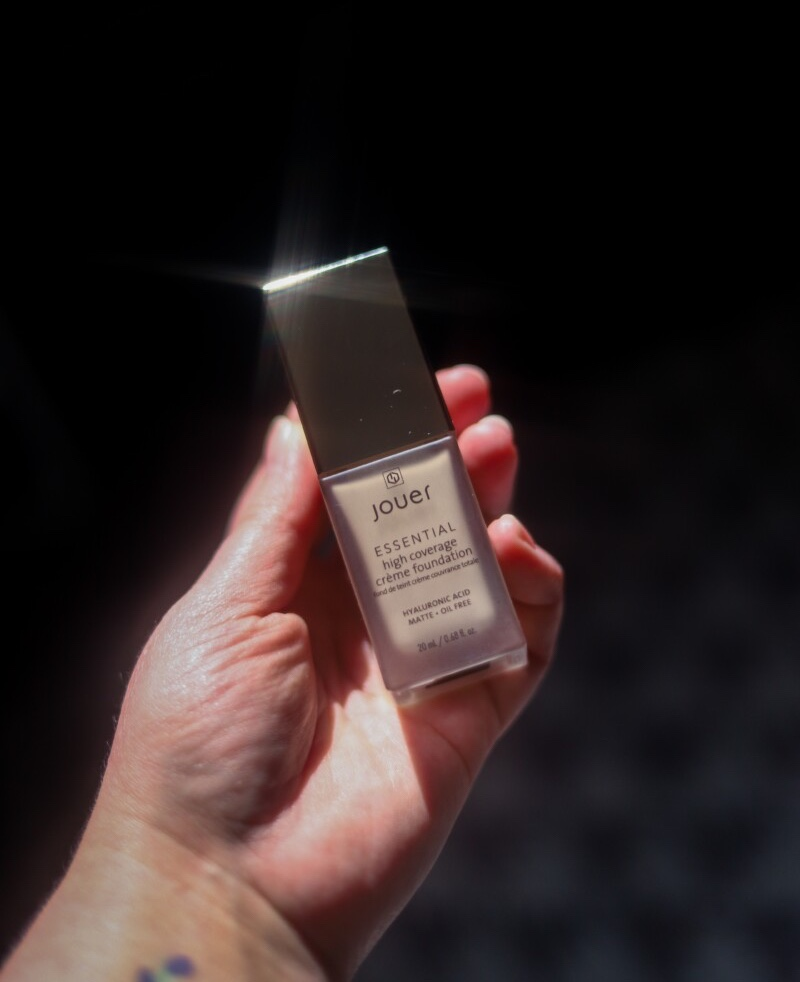 Jouer cosmetics high coverage foundation being held in hand with bright sunlight
