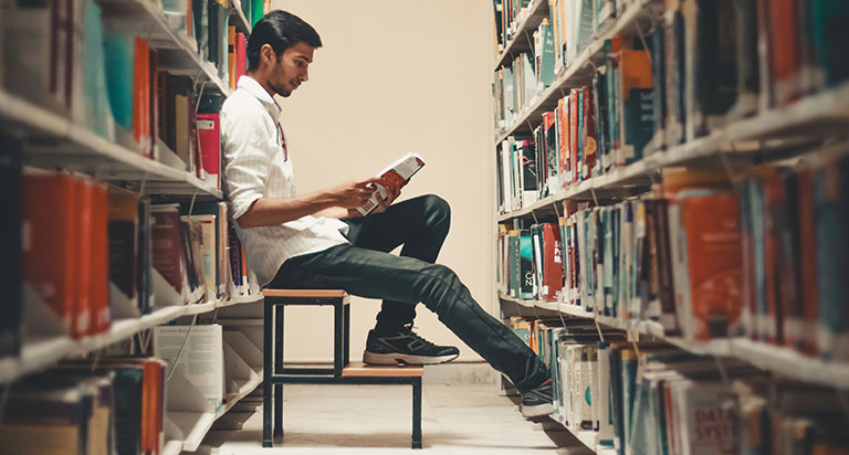 A young Afghan-looking man in a library, sitting between aisles, reading a book.