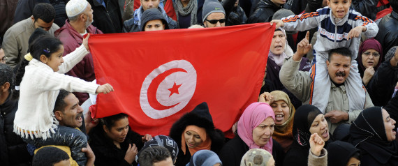 "People shout slogans and hold flags of Tunisia during a demonstration to demand jobs and dignity as the north African country marks a year to the day since its despot Zine El Abidine Ben Ali fled into exile on January 14, 2012 on Habib Bourguiba Avenue in Tunis. Some demonstrators, wearing the red and white of the national flag, called for recognition of the ""martyrs"" killed during the weeks of unrest before Ben Ali was toppled. AFP PHOTO / FETHI BELAID (Photo credit should read FETHI BELAID/AFP/Getty Images)"