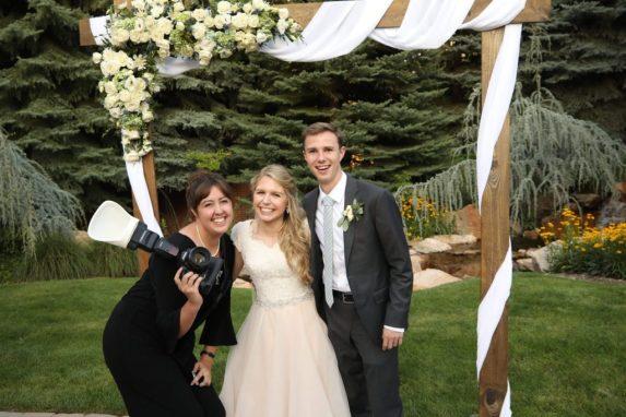 Kaci Lou of Kaci Lou Photography with a wedding couple, behind the scenes wedding photographer.