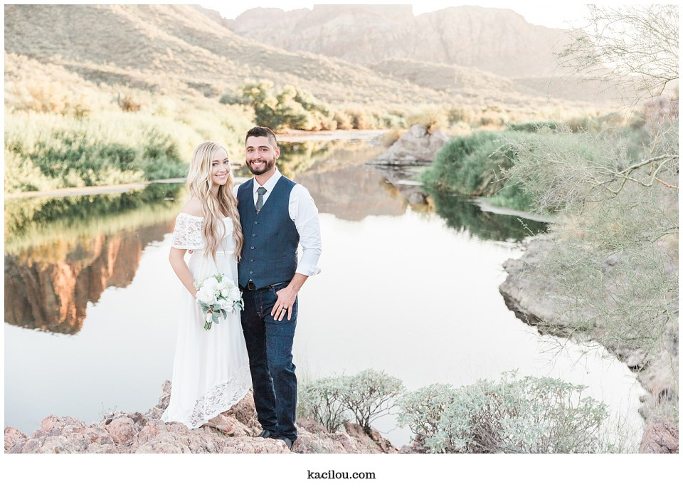 Salt river elopement photo of bride and groom smiling over mouth of river