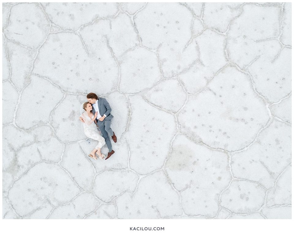 bride in jumpsuit on ground being held by groom in grey suit over white salt flats ground