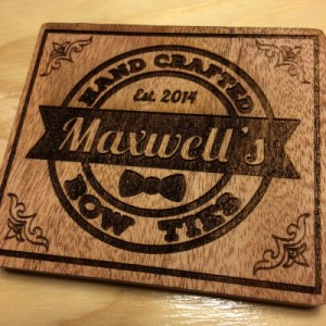 Maxwell's Bow Ties logo engraved on wood.