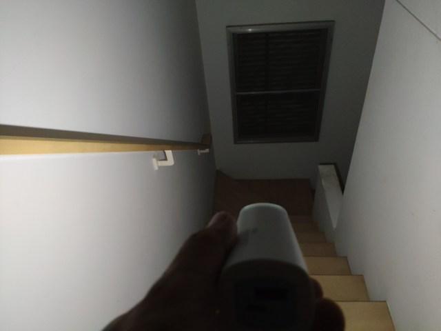 มือกำลังถือพาวเวอร์แบงก์และเปิดโหมดไฟฉายเพื่อส่องสว่างตรงบันไดทางลง