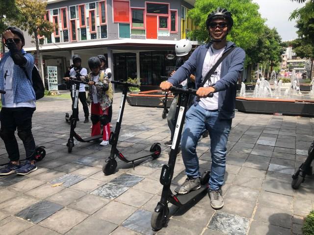 ภาพของตัวผมเอง สวมหมวกกันน็อกสำหรับจักรยาน และแว่นกันแดด ยืนอยู่บนสกู๊ตเตอร์ไฟฟ้า