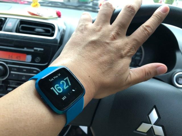 ข้อมือข้างซ้าย ที่กำลังสวมสมาร์ทวอทช์ Fitbit Versa Lite Edition สีน้ำเงินอยู่ กำลังวางมือบนพวงมาลัยรถยนต์