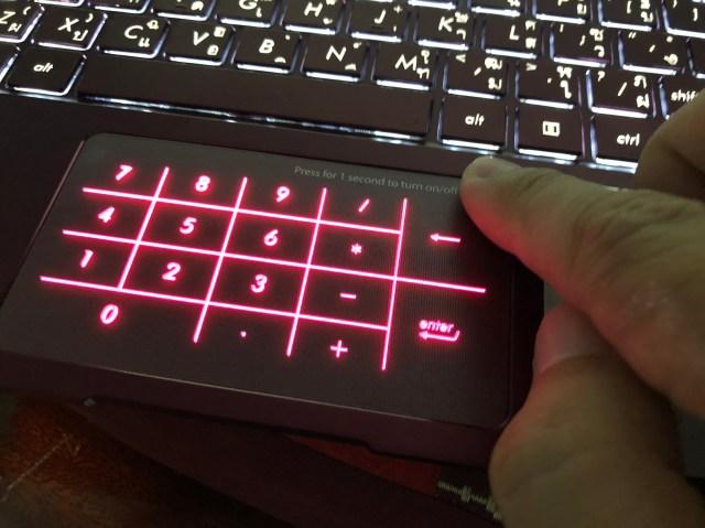 ภาพของนิ้วมือที่กำลังแตะปุ่มเปิดใช้งาน Num Pad บน TouchPad