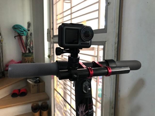 ตัวกล้อง DJI Osmo Action ถูกยึดอยู่บนแฮนด์ของสกู๊ตเตอร์ไฟฟ้า