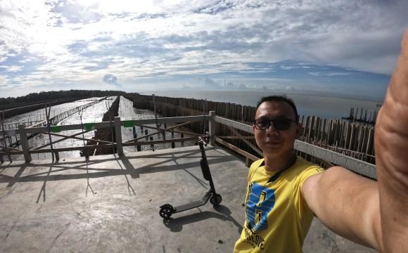 ผู้ชายใส่แว่น ใส่เสื้อสีเหลืองมีตัวอักษร B กำลังถ่ายเซลฟี่อยู่ที่ชายทะเล มีสกู๊ตเตอร์ไฟฟ้าจอดอยู่ห่างๆ