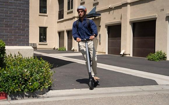 ภาพของผู้ชายชาวต่างชาติกำลังขี่สกู๊ตเตอร์ไฟฟ้าบนถนน